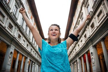 Happy fitness woman rejoicing near uffizi gallery in florence