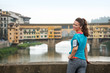 Smiling fitness woman standing in front of ponte vecchio