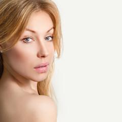 Портрет красивой молодой светловолосой женщины на сером фоне.