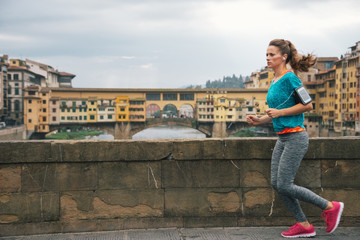 Fitness woman jogging in front of ponte vecchio in florence