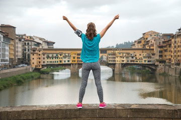 Fitness woman rejoicing in front of ponte vecchio in florence
