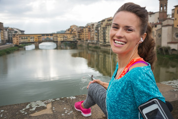 Portrait of happy fitness woman in front of ponte vecchio
