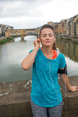 Fitness woman listening music in front of ponte vecchio