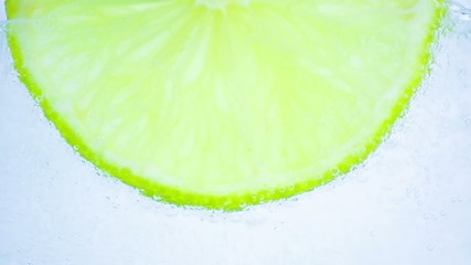 water in the glass with bubbles and lime on white background