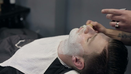 Barber shaves the beard of the client in the barbershoparbershop
