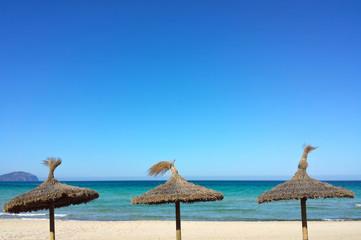 Trois parasols en paille sur la plage