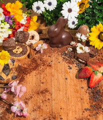 Dolci di Pasquacon fiori e cacao su un piano di legno