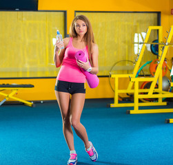 Beautiful woman with a yoga mat and bottle of water at the gym