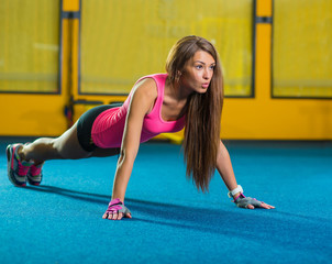 Gorgeous brunette warming up and doing some push ups a the gym