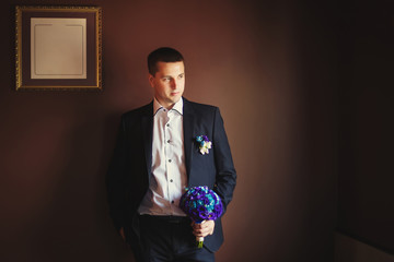 Young groom with wedding bouquet of flowers in dark brown interi