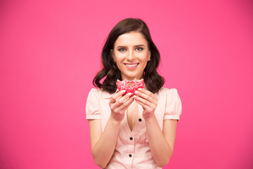 Happy woman eating donut and looking at camera