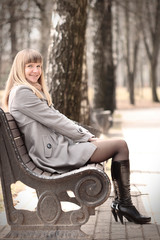 Young woman sitting on bench smiling