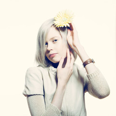 strange slim blonde girl with a yellow flower in her hair.