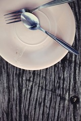 pink plate, knife and fork at napkin on wooden background