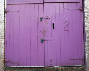 A large wooden double door painted purple
