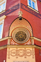 Old clock on the wall in the old town of Warsaw