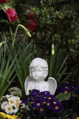 Friedhofsengel zwischen Blumen im Frühling