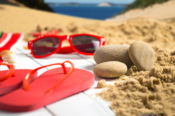 Stone^ flip flop and sunglasses on sandy pier near ocean