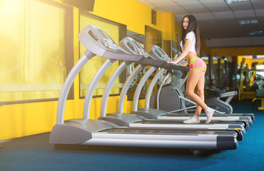 attractive young woman runs on a treadmill, is engaged in fitnes