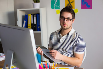 Young Handsome Graphic designer using graphics tablet to do his