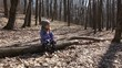 Cute Girl Sitting on Old Pine Tree in Early Spring Forest and Pl