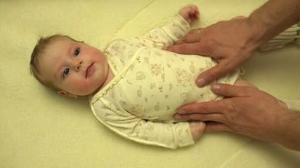 Man Hands Massaging Newborn Baby Body. Closeup