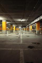 Image of parking garage underground interior, dark industrial bu