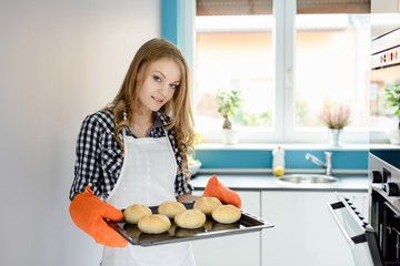 Young woman holding a baking tray with bread rolls