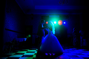 Silhouette of a bride and groom dancing a slow dance in the rest