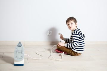 Boy playing dangerously with electric wire