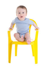 funny baby boy toddler sitting on little chair isolated on white