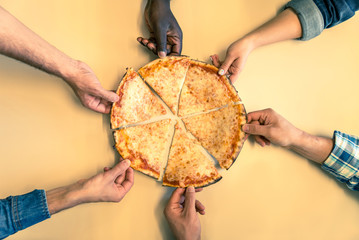 Six friends sharing a pizza in a restaurant