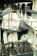 Kitchen Woman with a clean wine glass on background dishwasher