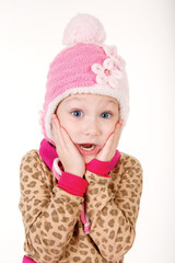 Cute little girl in red hat holding hands to face in surprise