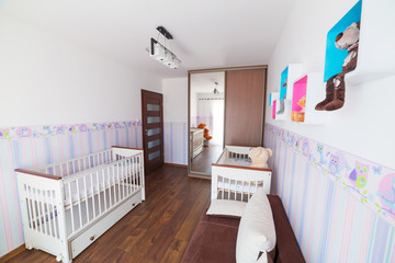 Bright baby room with pastel wallpapers and white cradles