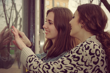 Two girls look into a shop window