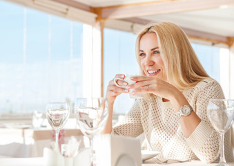 Young woman with cup of coffee in cafe