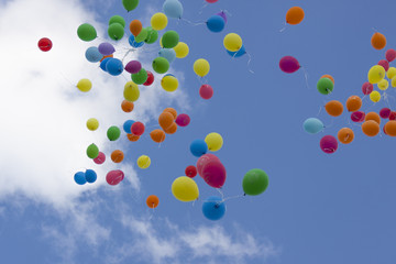 colorful balloons filled with helium fly in the blue sky
