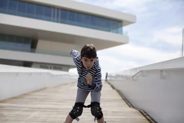 Niño bajando con patines rampa de madera