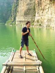 Man floating on a bamboo raft