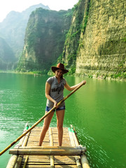 Pretty girl floating on a bamboo raft