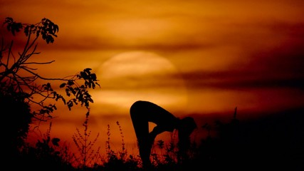 woman doing yoga at the sunset