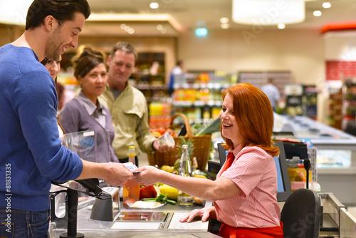 Leinwanddruck Bild Kundschaft beim bezahlen an der Kasse im Supermarkt