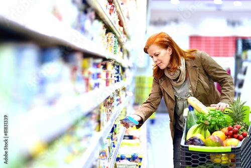 Leinwanddruck Bild - Frau kauft Lebenmittel im Supermarkt ein -