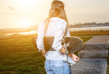 Skater young woman on sunset. Woman with skateboard in her hands