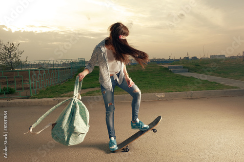 speeding skateboarding woman at city with backpack in her hands - 81831964