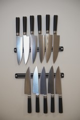 Set of knifes are hanging on kitchen wall