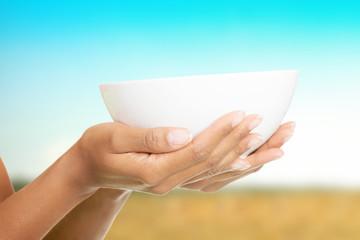 Woman holding empty bowl.