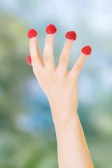 Woman's hand with raspberries.