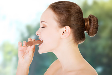 Young woman eating a chocolate bar.